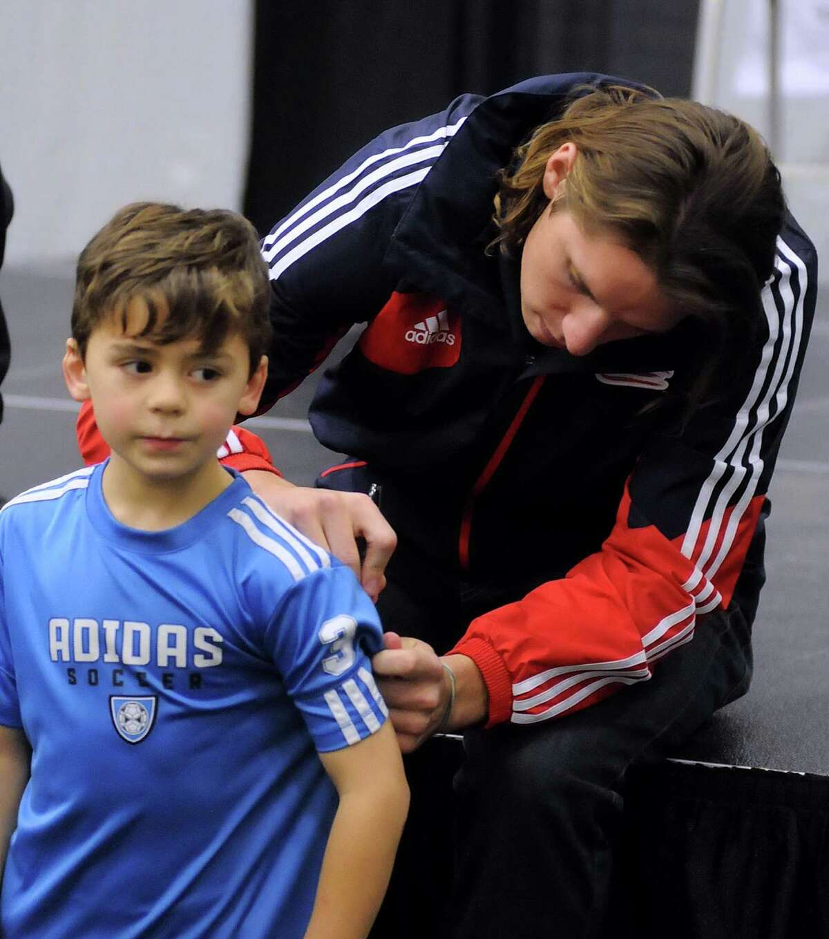 American soccer player, Bobby Shuttleworh, signs the back of eight-year old Nicholas Psichopaidas' shirt during the Soccer Night in Newtown on Monday Jan. 7, 2013.