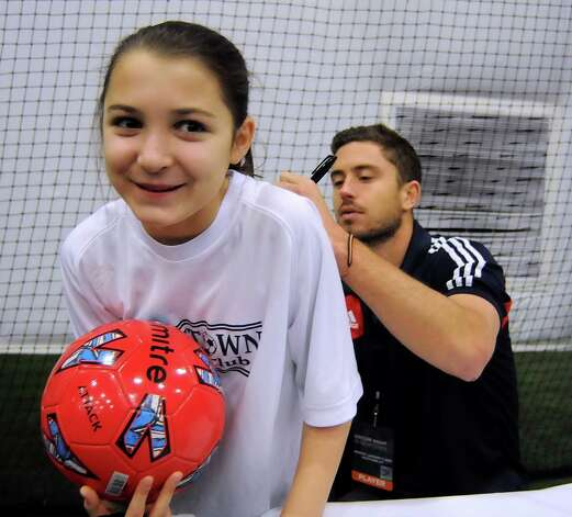 American soccer player, Chris Tierney, signs the back of 11-year old Rose Duval during the Soccer Night in Newtown on Monday Jan. 7, 2013. Photo: Lisa Weir