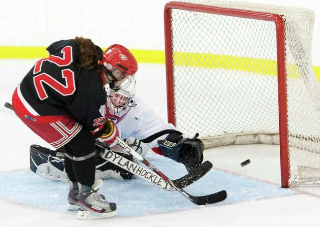 New Canaan high school's Olivia Hompe gets a shot by Greenwich high school goalie Dart Freccia in a girls ice hockey game played at the Dorothy Hamill Skating Rink, Greenwich, CT on Monday January 7th, 2013. Photo: Mark Conrad / Stamford Advocate Freelance