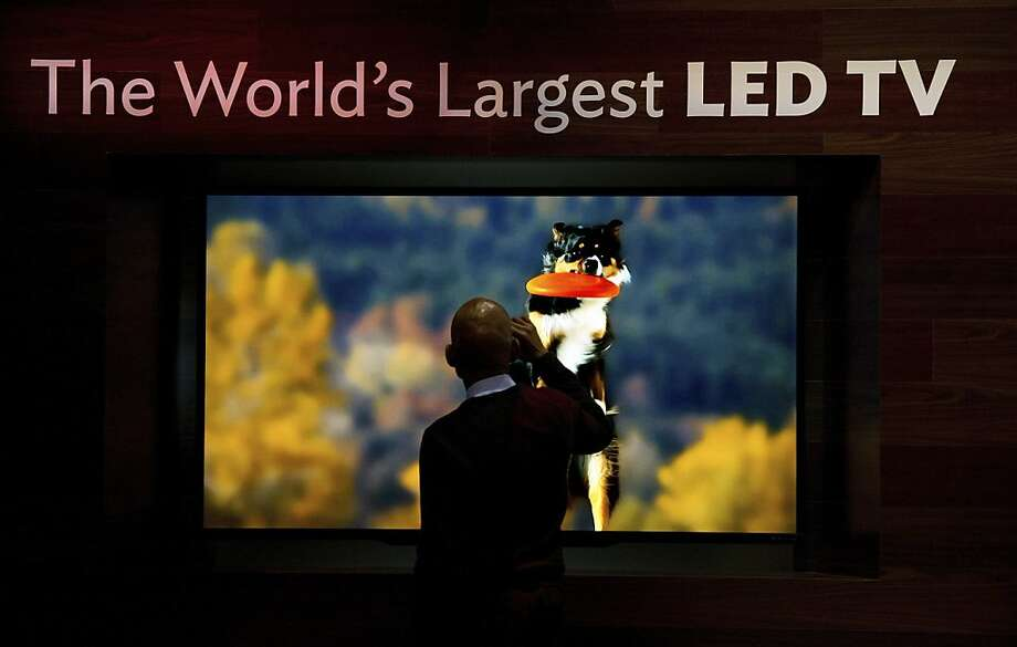 A spectator stops to take a photograph of a Sharp Corp., television on display prior to the 2013 Consumer Electronic Show in Las Vegas, Nevada, U.S., on Monday, Jan. 7, 2013. The 2013 CES trade show, which runs until Jan. 11, is the world's largest annual innovation event that offers an array of entrepreneur focused exhibits, events and conference sessions for technology entrepreneurs. Photographer: David Paul Morris/Bloomberg Photo: David Paul Morris, Bloomberg