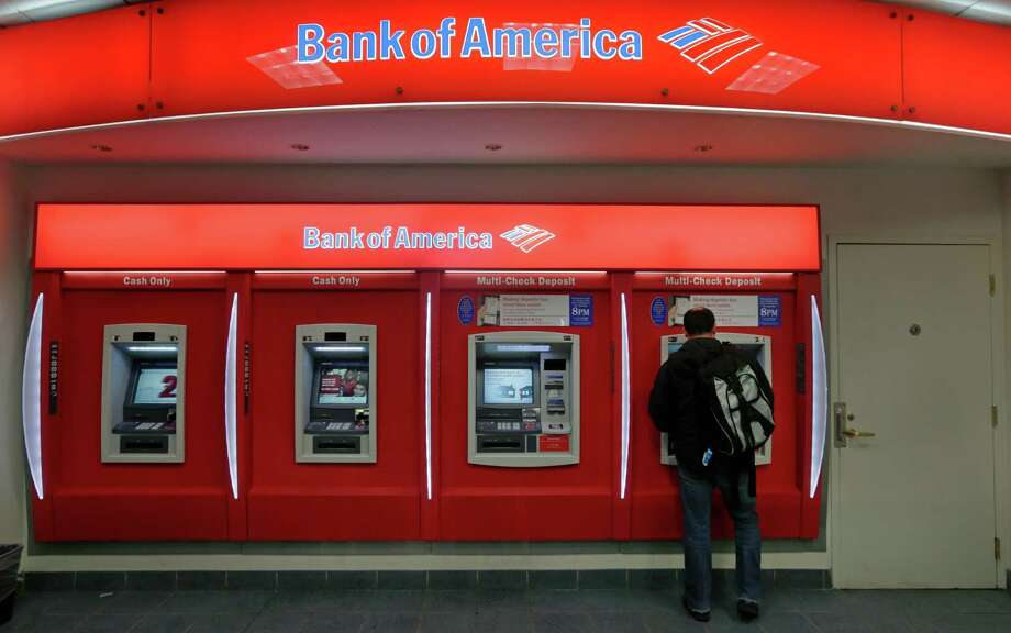 In this Dec. 13, 2012 photo, a customer stops at a Bank of America ATM office in Boston. Bank of America Corp. says it will spend more than $10 billion to settle mortgage claims resulting from the housing meltdown. Under the deal announced Monday, Jan. 7, 2013, the bank will pay $3.6 billion to Fannie Mae and buy back $6.75 billion in loans that the North Carolina-based bank and its Countrywide banking unit sold to the government agency from Jan. 1, 2000 through Dec. 31, 2008. That includes about 30,000 loans. (AP Photo/Charles Krupa) Photo: Charles Krupa