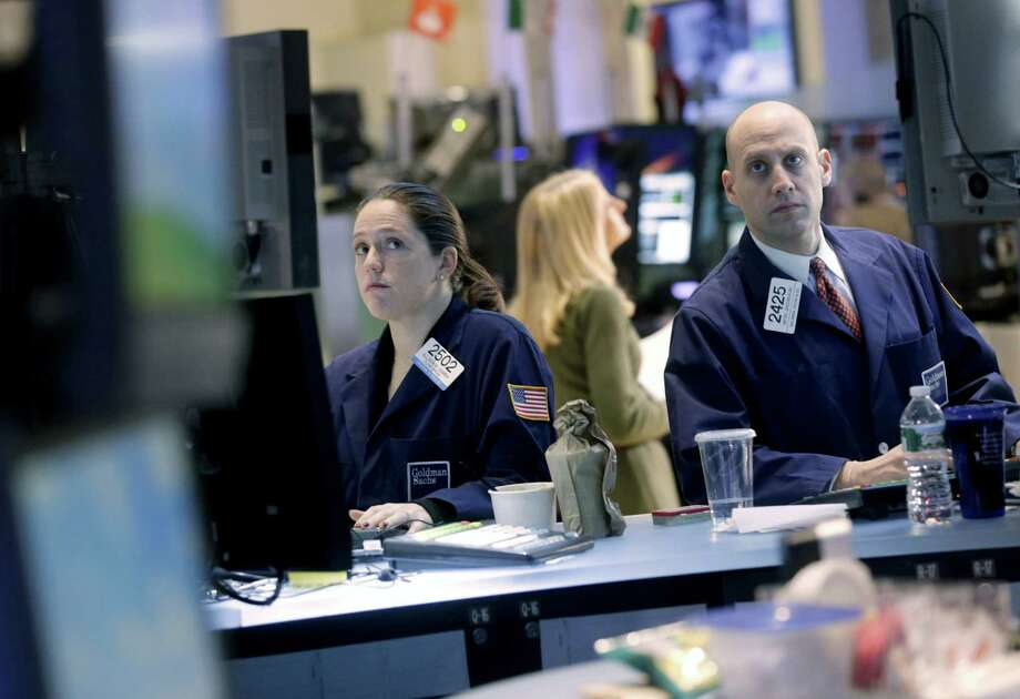 Traders work on the floor at the New York Stock Exchange in New York, Monday, Dec. 31, 2012. World stocks cooled off Monday Jan. 7, 2013 as some investors sold shares to lock in profits following recent rallies.  (AP Photo/Seth Wenig) Photo: Seth Wenig
