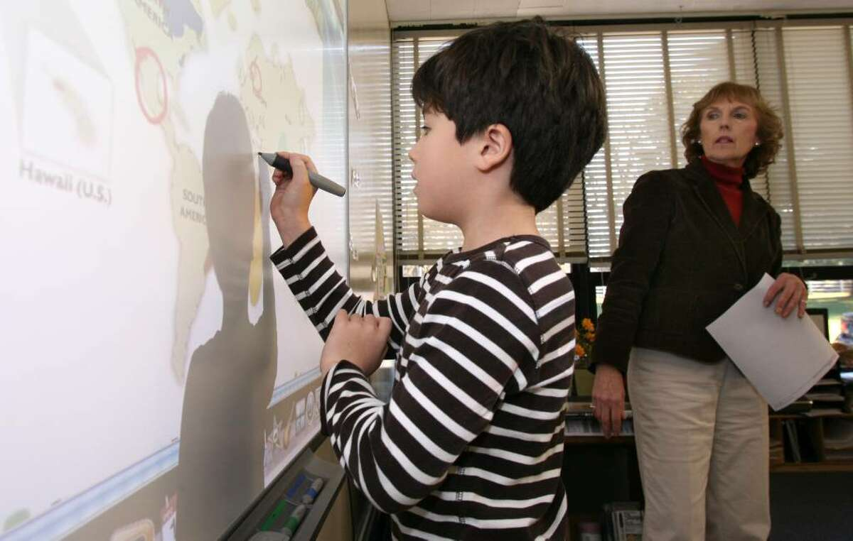 North Street School first grader Jude Stiel works at a SmartBoard as media specialist Terese Case looks on.