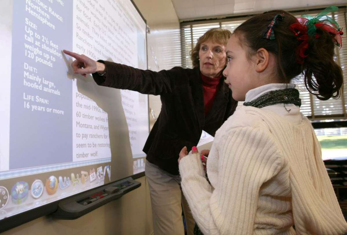 North Street School first grader Sydney Petrone gets instruction on a SmartBoard by librarian and media specialist Terese Case during a class Friday morning.
