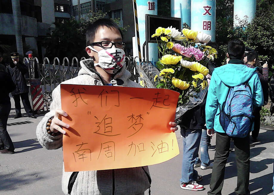 "In this photo taken and provided by activist Wu Wei, a man wearing a mask with words ""Silent"" holds a banner reading: ""Let's chase our dreams together, go Southern Weekly newspaper"" during a protest outside the headquarters of the newspaper in Guangzhou, Guangdong province Monday, Jan. 7, 2013. A dispute over censorship at the Chinese newspaper known for edgy reporting has prompted a few hundred people to gather in a rare street protest urging Communist Party leaders to allow greater political freedom. (AP Photo/Wu Wei) EDITORIAL USE ONLY Photo: Wu Wei"