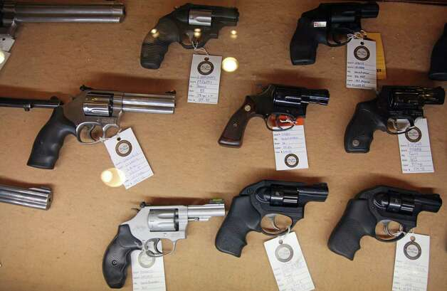 In this Jan. 4, 2013, photo, handguns are displayed in the sales area of Sandy Springs Gun Club and Range, in Sandy Springs, Ga. In Connecticut and Colorado, scenes of the most deadly U.S. mass shootings in 2012, people were less enthusiastic about buying new guns at the end of the year than in most other states, according to an Associated Press analysis of new FBI data. The biggest surges in background checks for people who want to carry or buy guns occurred in states in the South and West. (AP Photo/Robert Ray) Photo: Robert Ray