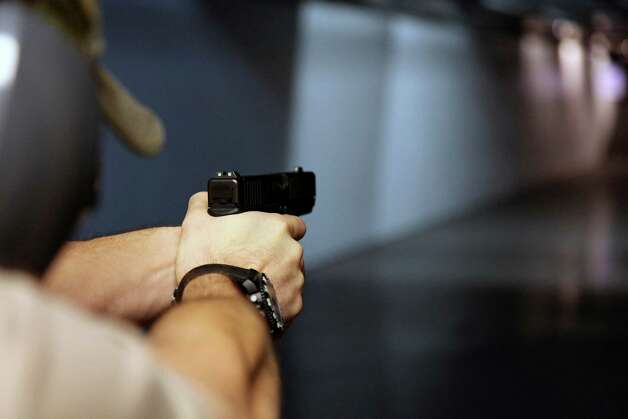 In this Jan. 4, 2013, photo, a man fires a hand gun at Sandy Springs Gun Club and Range, in Sandy Springs, Ga. In Connecticut and Colorado, scenes of the most deadly U.S. mass shootings in 2012, people were less enthusiastic about buying new guns at the end of the year than in most other states, according to an Associated Press analysis of new FBI data. The biggest surges in background checks for people who want to carry or buy guns occurred in states in the South and West. (AP Photo/Robert Ray) Photo: Robert Ray