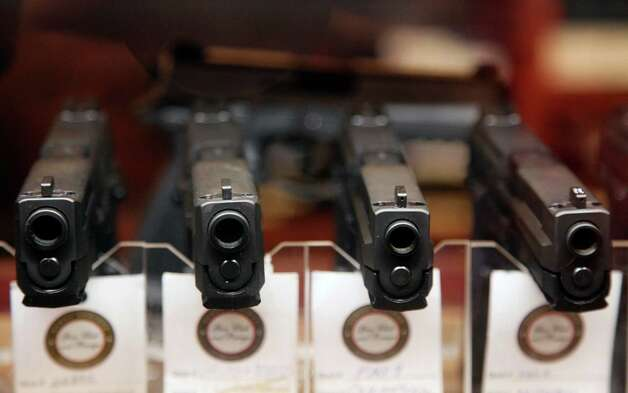 In this Jan. 4, 2013 photo, handguns are displayed in the sales area of Sandy Springs Gun Club and Range, in Sandy Springs, Ga. In Connecticut and Colorado, scenes of the most deadly U.S. mass shootings in 2012, people were less enthusiastic about buying new guns at the end of the year than in most other states, according to an Associated Press analysis of new FBI data. The biggest surges in background checks for people who want to carry or buy guns occurred in states in the South and West. (AP Photo/Robert Ray) Photo: Robert Ray