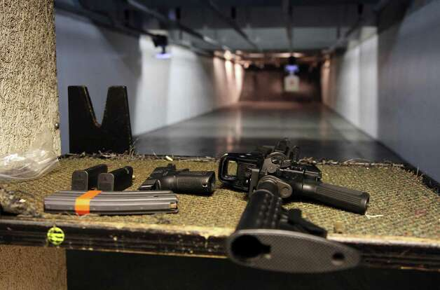 In this Jan. 4, 2013, photo, a rifle and a hand gun are displayed on the range of Sandy Springs Gun Club and Range, in Sandy Springs, Ga. In Connecticut and Colorado, scenes of the most deadly U.S. mass shootings in 2012, people were less enthusiastic about buying new guns at the end of the year than in most other states, according to an Associated Press analysis of new FBI data. The biggest surges in background checks for people who want to carry or buy guns occurred in states in the South and West. (AP Photo/Robert Ray) Photo: Robert Ray