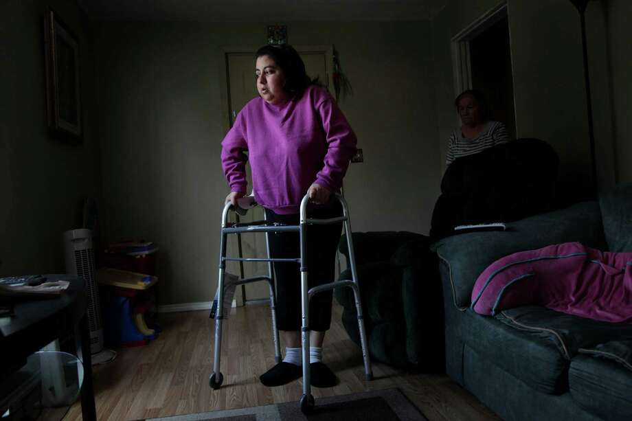 Maria Sanchez, 25, struggled to walk in her living room in February due to the tumor on her spinal cord, as her mother-in-law, Blanca Aguillon, watched. Sanchez was discharged from a hospital due to her immigration status. Photo: Mayra Beltran, Staff / © 2012 Houston Chronicle