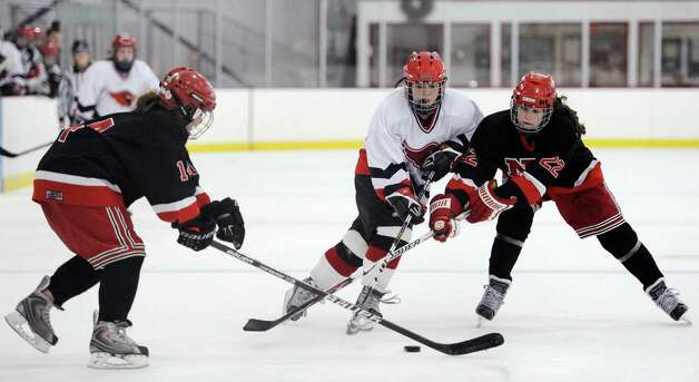 New Canaan high school's Madeline Carroll (14) and Olivia Hompe (22) battle Greenwich high school's Erin Fergusonx in a girls ice hockey game played at the Dorothy Hamill Skating Rink, Greenwich, CT on Monday January 7th, 2013. Photo: Mark Conrad / Stamford Advocate Freelance