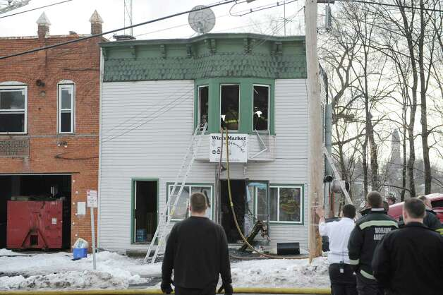 Firefighters work at the scene of a structure fire at 40 Partition St. on Monday, Jan. 7, 2013 in Rensselaer, N.Y.  The building houses Win's Market on the first floor.  (Paul Buckowski / Times Union) Photo: Paul Buckowski / 00020684A