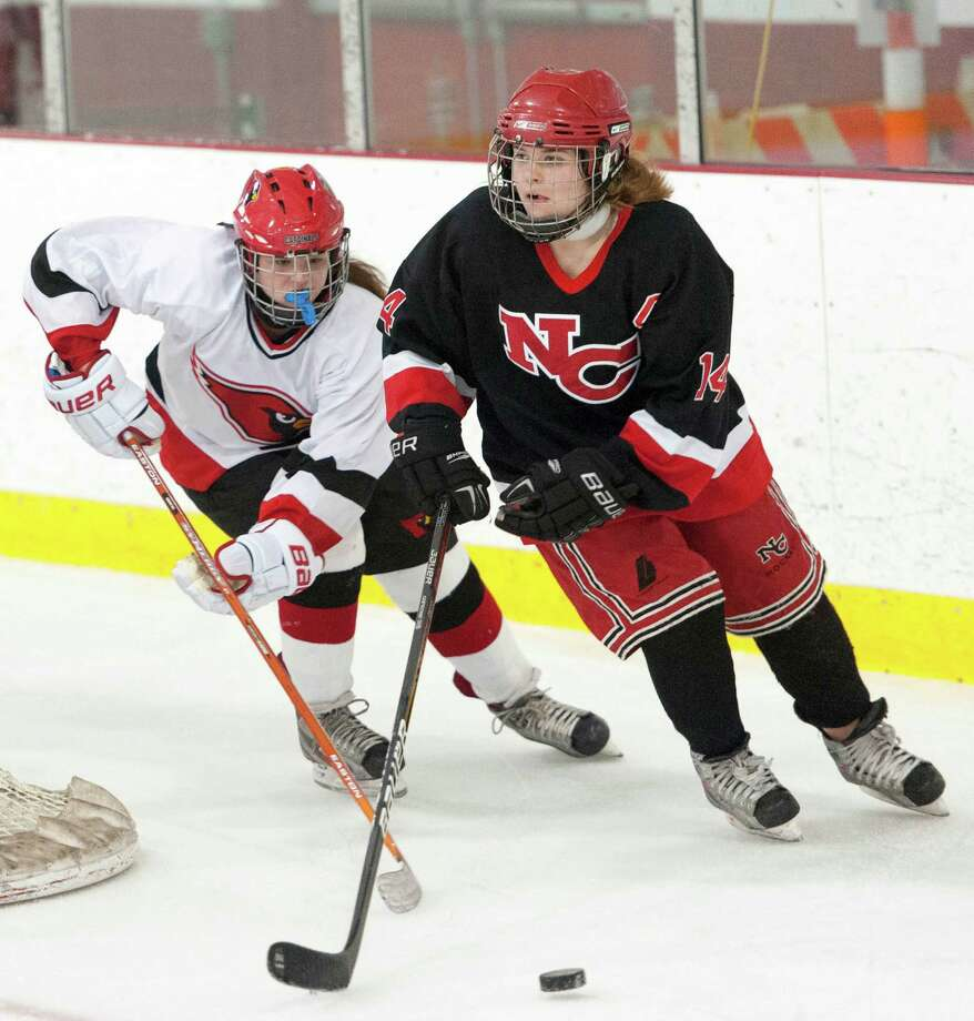 New Canaan high school's Madeline Carroll clears to puck out from behind the New Canaan goal in a girls ice hockey game against Greenwich high school played at the Dorothy Hamill Skating Rink, Greenwich, CT on Monday January 7th, 2013. Greenwich high school's Madeline Graves at left. Photo: Mark Conrad / Stamford Advocate Freelance