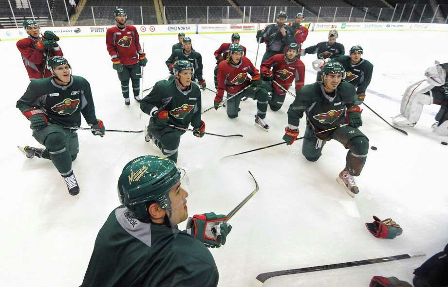 Wild players, including Devin Setoguchi, foreground, listen to instructions during Monday's informal workout at the Xcel Arena in St. Paul, Minn. Photo: Jim Mone, STF / AP