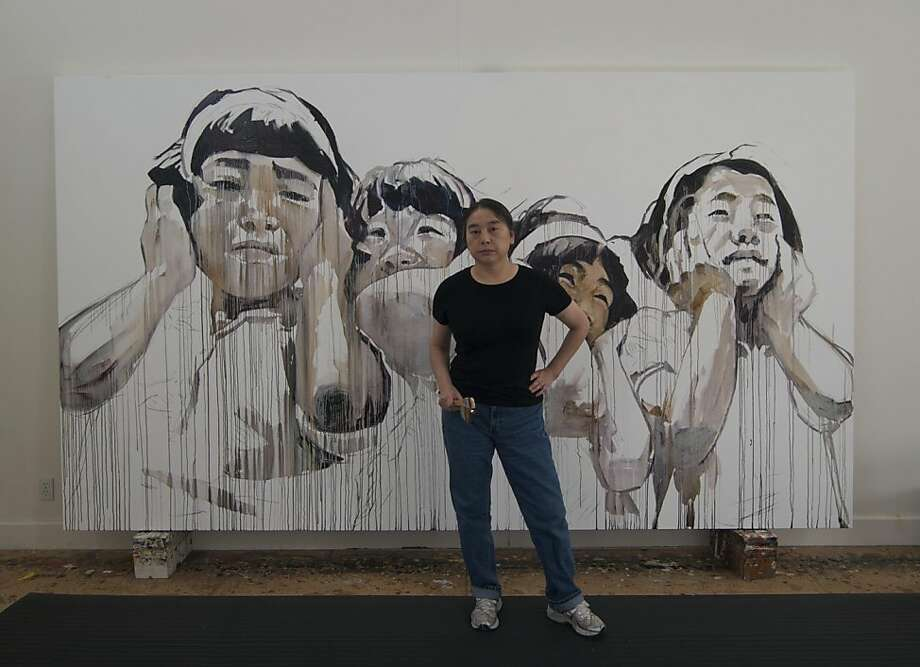 "Hung Liu's work is the subject of an Oakland Museum retrospective, ""Summoning Ghosts,"" in March. Here she poses with her 2010 painting ""Jingzhe First Spring Thunder."" Photo: Courtesy Of Hung Liu Jeff Kelley"