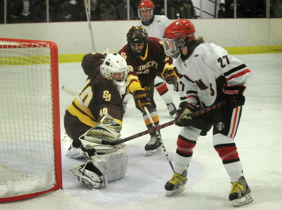 St. Joseph goalie Wade Conlan makes a save on New Canaan's Cooper Manchuck in the second period of their FCIAC hockey matchup at the Darien Ice Rink on Monday, January 7, 2013. Photo: Brian A. Pounds