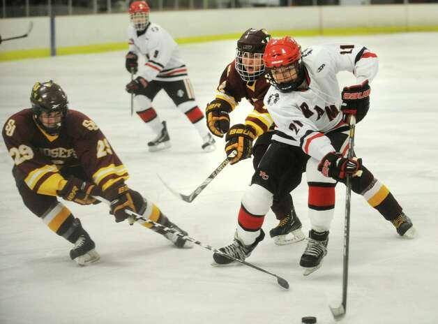 From left; St. Joseph's Tyler English and Troy Deering defend a rush from New Canaan's Parker Lewis in the second period of their FCIAC hockey matchup at the Darien Ice Rink on Monday, January 7, 2013. Photo: Brian A. Pounds