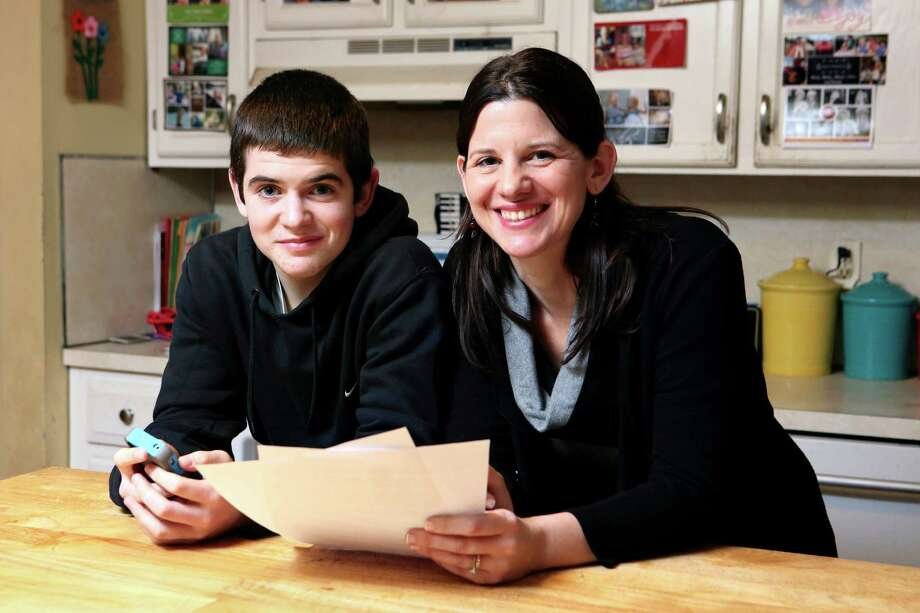 In this Jan. 4, 2013, photo, Janell Burley Hofmann, right, poses with her son Gregory at their home in Sandwich, Mass. Janell holds a copy of the contract she drafted and that Gregory signed as a condition for receiving his first Apple iPhone. (AP Photo/Michael Dwyer) Photo: Michael Dwyer