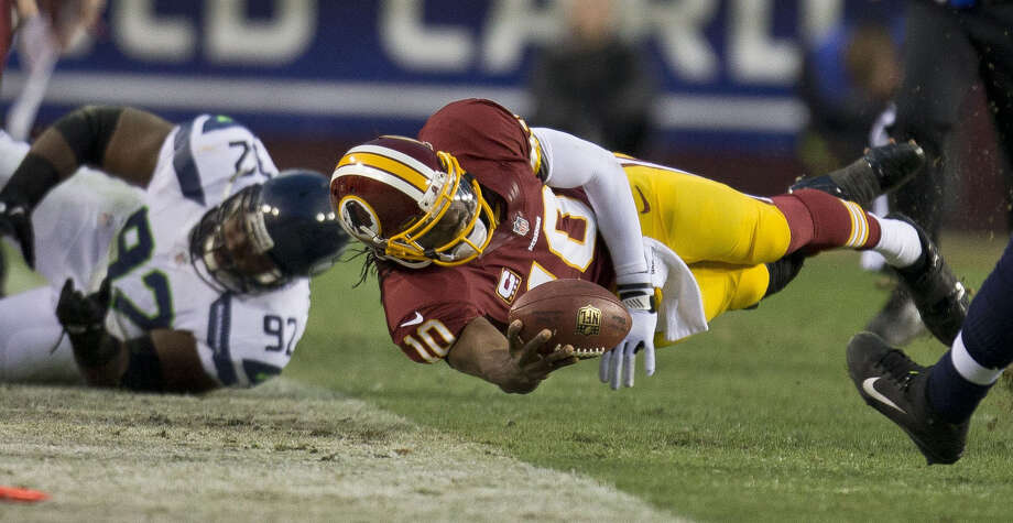 Washington Redskins quarterback Robert Griffin III dives for a first down in the first half of an NFL football wild card playoff game against the Seattle Seahawks on Sunday, Jan. 6, 2013, in Landover, Md. (AP Photo/The Seattle Times, Dean Rutz) SEATTLE OUT  MAGS OUT  NO SALES  MANDATORY CREDIT  TV OUT  USA TODAY OUT Photo: Dean Rutz / The Seattle Times