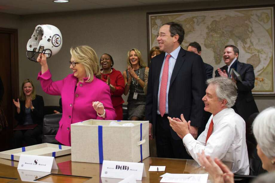 This handout photo provided by the State Department shows Secretary of State Hillary Rodham Clinton holding up a football helmet presented to her at the State Department in Washington, Monday, Jan. 7, 2013, as she returned to work on Monday after a month-long absence caused first by a stomach virus, then a fall and a concussion and finally a brief hospitalization for a blot clot near her brain. (AP Photo/State Department)