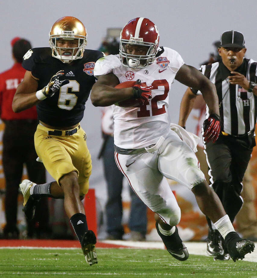 Alabama's Eddie Lacy (42) runs past Notre Dame cornerback KeiVarae Russell during the second half of the BCS National Championship college football game Monday, Jan. 7, 2013, in Miami. (AP Photo/John Bazemore) Photo: John Bazemore, Associated Press / AP