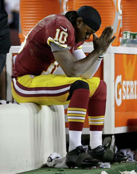 Redskins quarterback Robert Griffin III ponders his future after being injured in Sunday's playoff game. Photo: Evan Vucci, STF / AP