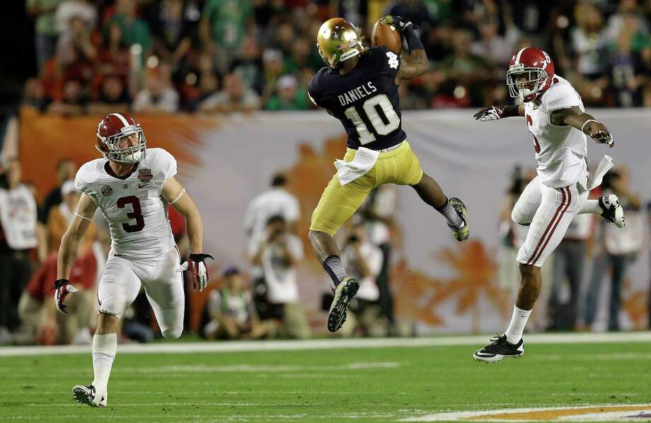 Notre Dame's DaVaris Daniels (10) catches a pass between Alabama's Vinnie Sunseri (3) and Ha'Sean Clinton-Dix during the first half of the BCS National Championship college football game Monday, Jan. 7, 2013, in Miami. (AP Photo/Wilfredo Lee) Photo: Wilfredo Lee, Associated Press / AP