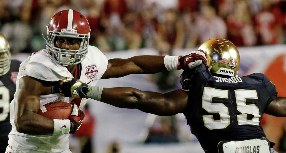 Alabama's T.J. Yeldon tries to get past Notre Dame's Prince Shembo (55) during the first half of the BCS National Championship college football game Monday, Jan. 7, 2013, in Miami. (AP Photo/David J. Phillip) Photo: David J. Phillip, Associated Press / AP