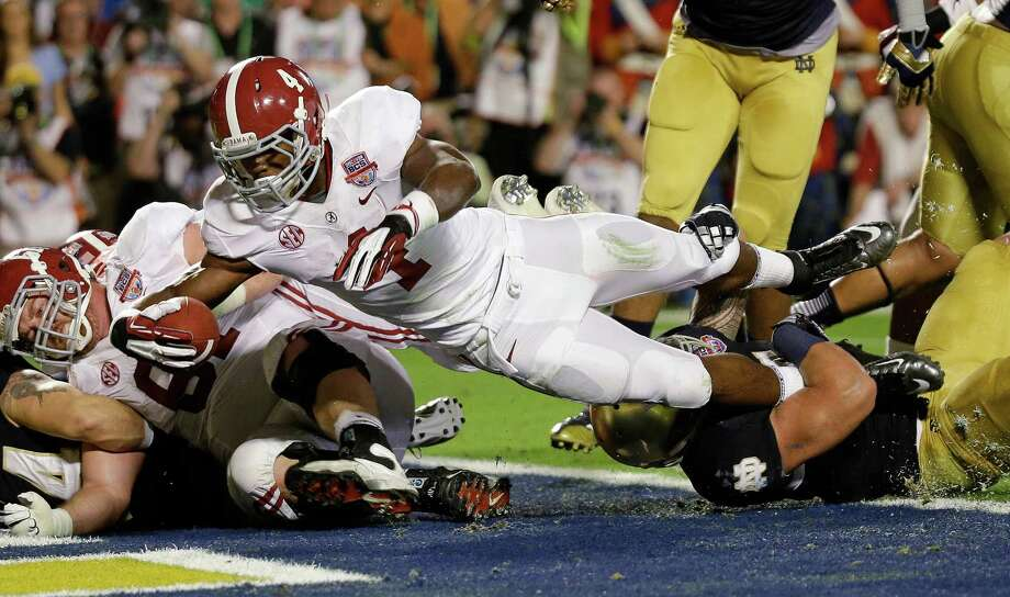 Alabama's T.J. Yeldon (4) dives into the end zone for a touchdown during the first half of the BCS National Championship college football game against Notre Dame Monday, Jan. 7, 2013, in Miami. (AP Photo/David J. Phillip) Photo: David J. Phillip, Associated Press / AP