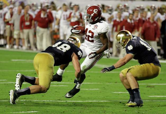 Alabama's Eddie Lacy spins past Notre Dame's Dan Fox (48) and Danny Spond for a touchdown during the first half of the BCS National Championship college football game Monday, Jan. 7, 2013, in Miami. (AP Photo/Chris O'Meara) Photo: Chris O'Meara, Associated Press / AP
