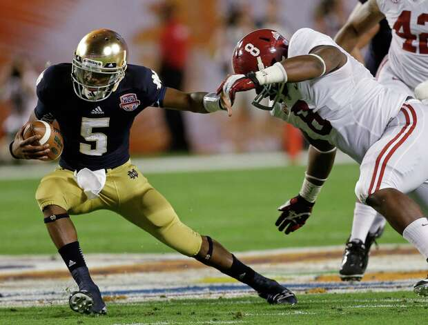 Notre Dame quarterback Everett Golson tries to get away from Alabama's Jeoffrey Pagan (8) during the first half of the BCS National Championship college football game Monday, Jan. 7, 2013, in Miami. (AP Photo/Chris O'Meara) Photo: Chris O'Meara, Associated Press / AP