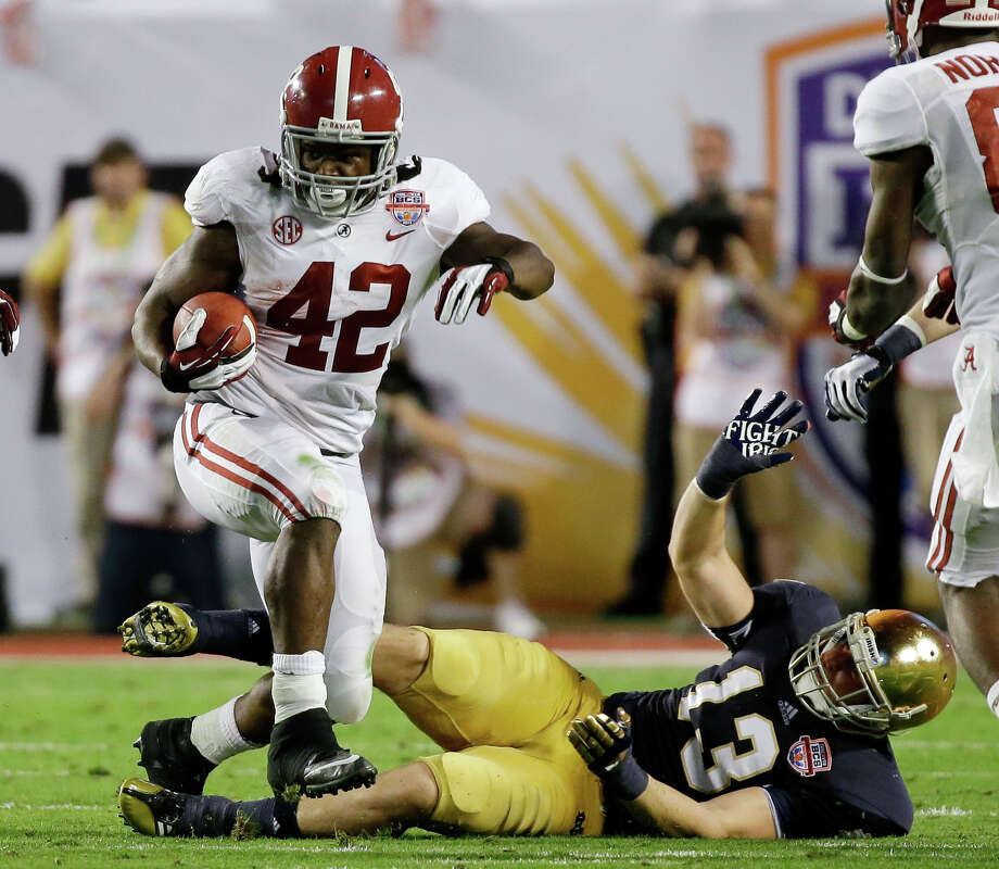 Alabama's Eddie Lacy (42) runs past Notre Dame's Danny Spond (13) during the first half of the BCS National Championship college football game Monday, Jan. 7, 2013, in Miami. (AP Photo/David J. Phillip) Photo: David J. Phillip, Associated Press / AP
