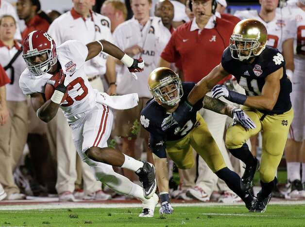 Alabama's Kevin Norwood (83)catches a pass in front of Notre Dame's Bennett Jackson (2) and Matthias Farley (41) during the first half of the BCS National Championship college football game Monday, Jan. 7, 2013, in Miami. (AP Photo/Chris O'Meara) Photo: Chris O'Meara, Associated Press / AP