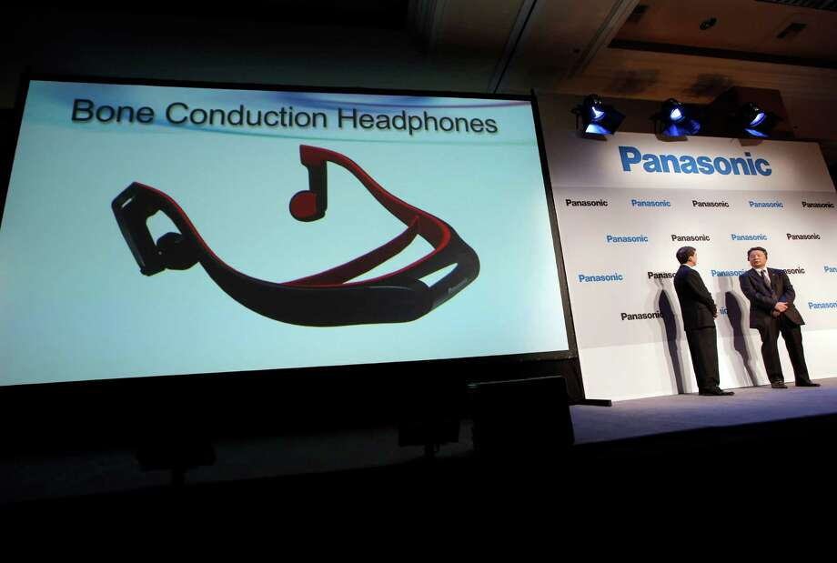 Panasonic's Shiro Kitajima, far right, and Vic Carlson, introduces the bone construction headphones during a news conference at the International Consumer Electronics Show in Las Vegas, Monday, Jan. 7, 2013. The headphones connect to a TV via the Bluetooth wireless standard and attach to your head like a normal set of headphones. But instead of using your ears, the headphones work like hearing aids by transmitting sound waves through your skull. (AP Photo/Jae C. Hong) Photo: Jae C. Hong, STF / AP