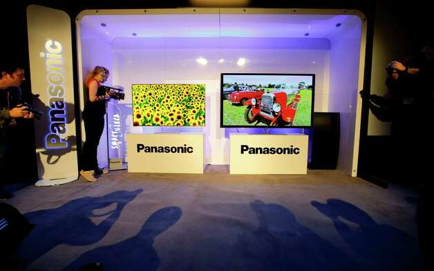 Show attendees photograph Panasonic's new televisions during a news conference at the International Consumer Electronics Show in Las Vegas, Monday, Jan. 7, 2013. The 2013 International CES gadget show, the biggest trade show in the Americas, is taking place in Las Vegas this week. (AP Photo/Jae C. Hong) Photo: Jae C. Hong, STF / AP