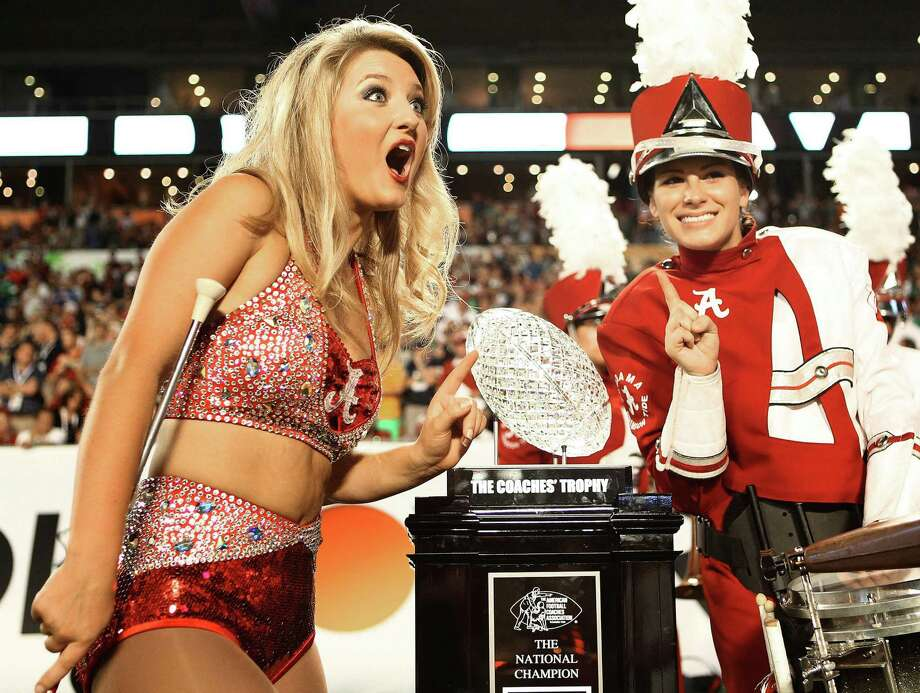 An Alabama cheerleader reacts while posing for a photograph with the BCS trophy at the start of the BCS Championship game against Notre Dame at Sun Life Stadium on Monday, January 7, 2013, in Miami Gardens, Florida. (Bill Ingram/Palm Beach Post/MCT) Photo: Bill Ingram, McClatchy-Tribune News Service / Palm Beach Post