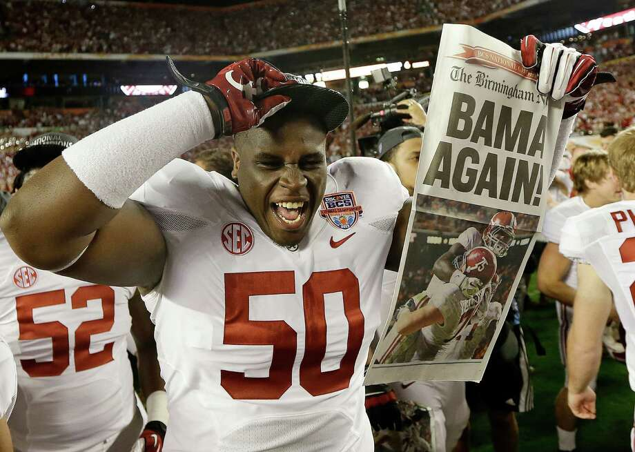 Alabama defensive lineman Alphonse Taylor (50) holds up a newspaper after the BCS National Championship college football game Monday, Jan. 7, 2013, in Miami. Alabama won 42-14. (AP Photo/David J. Phillip) Photo: David J. Phillip, Associated Press / AP