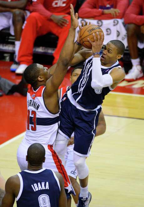 Thunder guard Russell Westbrook, who had 17 points, struggles to get a shot off against Wizards forward Kevin Seraphin. Photo: Harry E. Walker / MCT