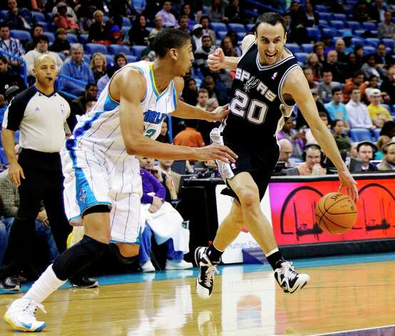 Spurs guard Manu Ginobili (20) breaks free from New Orleans Hornets forward Anthony Davis (23) in the first half  in New Orleans, Monday, Jan. 7, 2013. Photo: Bill Haber, Associated Press / FR170136 AP