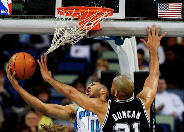 New Orleans Hornets shooting guard Eric Gordon (10) goes up for a shot as Spurs power forward Tim Duncan (21) tries for the block  in the first half   in New Orleans, Monday, Jan. 7, 2013. Photo: Bill Haber, Associated Press / FR170136 AP