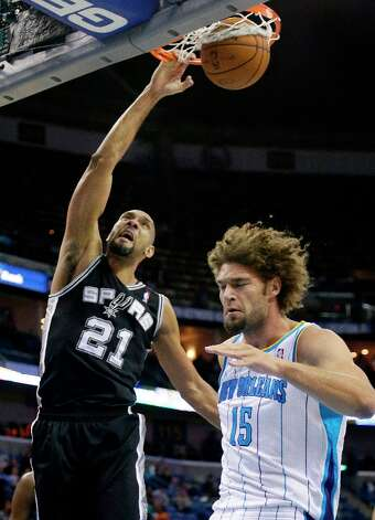 San Antonio Spurs power forward Tim Duncan (21) dunks over New Orleans Hornets center Robin Lopez (15) in the first half of an NBA basketball game  in New Orleans, Monday, Jan. 7, 2013. (AP Photo/Bill Haber) Photo: Bill Haber, Associated Press / FR170136 AP