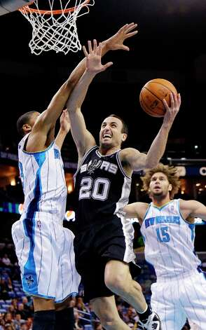 Spurs guard Manu Ginobili (20) drives to the basket around New Orleans Hornets forward Anthony Davis, left, as center Robin Lopez (15) watches in the first half in New Orleans, Monday, Jan. 7, 2013. Photo: Bill Haber, Associated Press / FR170136 AP