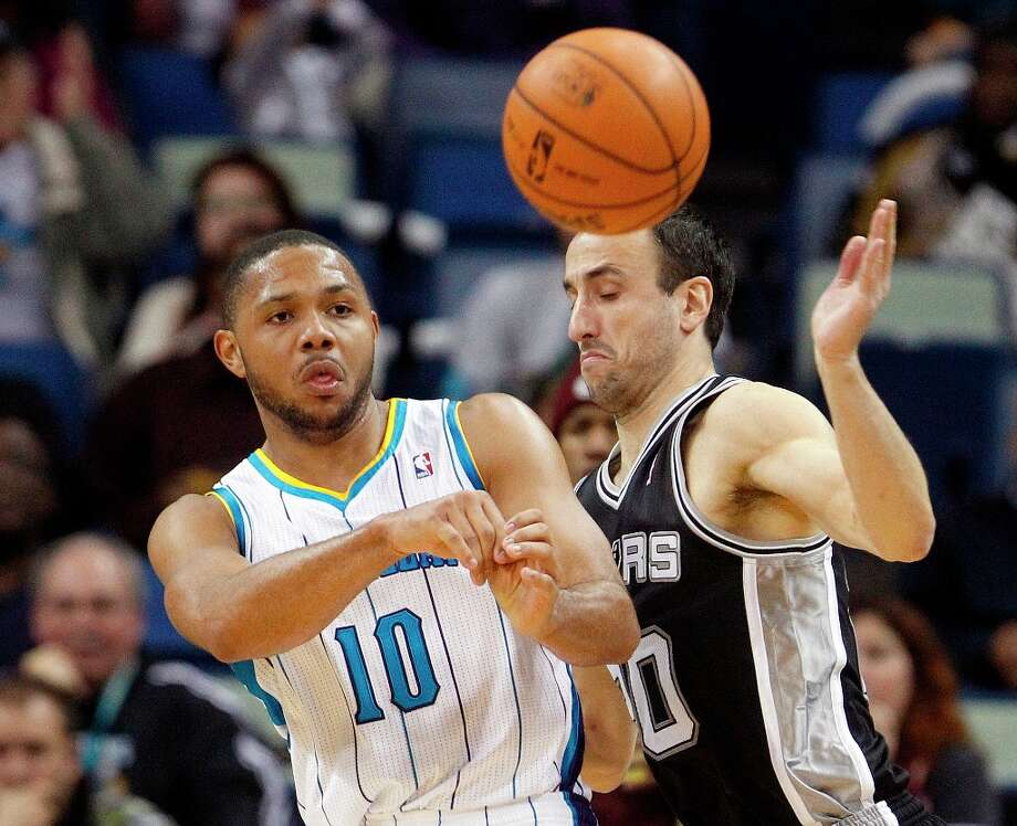 New Orleans Hornets guard Eric Gordon (10) passes the ball as  Spurs guard Manu Ginobili (20) plays defense in the second half   in New Orleans, Monday, Jan. 7, 2013. Photo: Bill Haber, Associated Press / FR170136 AP