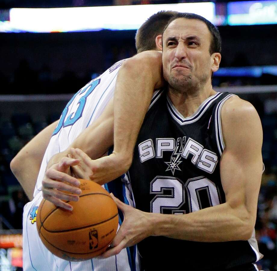Spurs guard Manu Ginobili (20) is fouled by New Orleans Hornets forward Ryan Anderson (33) in the second half  in New Orleans, Monday, Jan. 7, 2013. The Hornets defeated the Spurs 95-88. Photo: Bill Haber, Associated Press / FR170136 AP