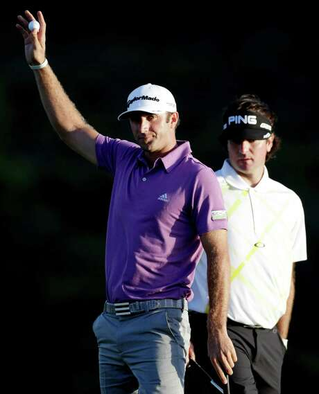 Dustin Johnson, playing with Bubba Watson, acknowledges the gallery after an eagle on No. 18. Photo: Elaine Thompson, STF / AP