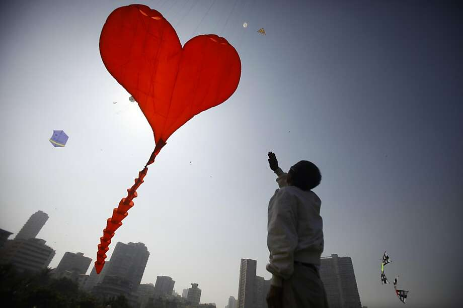 A participant from New Zealand flies a large heart shaped kite at the International Kite Festival in Mumbai, India, Monday, Jan. 7, 2012. Kite-flyers from different countries are participating in the day-long festival. Photo: Rafiq Maqbool, Associated Press