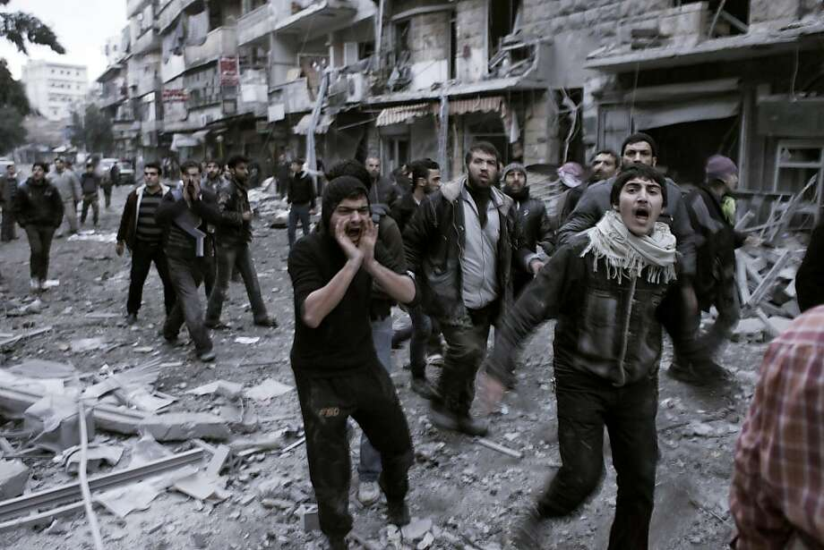 "Syrians shout slogans as they rush to the location of a building targeted by a missile in the al-Mashhad neighbourhood of Aleppo on January 7, 2013. The United Nations recently denounced a ""proliferation of serious crimes including war crimes"" in Syria, as ever more horrifying images and videos emerge from the country. Photo: -, AFP/Getty Images"