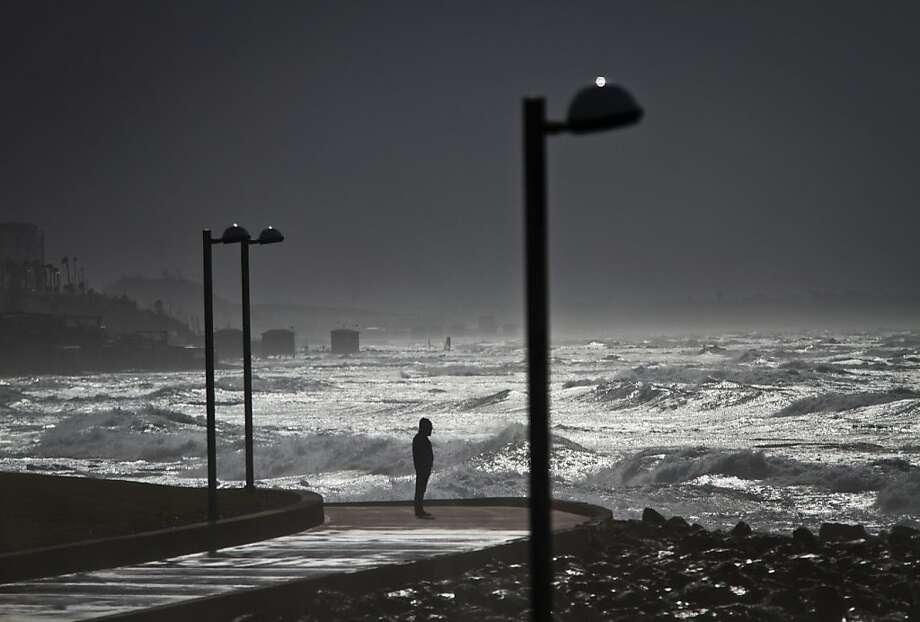 A person looks at waves of the Mediterranean sea in Tel Aviv, Israel, Monday, Jan. 7, 2013. Wind gusts reached up to 40mph, as waves reached 9 meters high (30 feet). Photo: Ariel Schalit, Associated Press