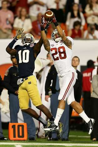 MIAMI GARDENS, FL - JANUARY 07:  Dee Milliner #28 of the Alabama Crimson Tide breaks up a pass intended for DaVaris Daniels #10 of the Notre Dame Fighting Irish causing Ha'Sean Clinton-Dix #6 of the Alabama Crimson Tide to intercept it during the 2013 Discover BCS National Championship game at Sun Life Stadium on January 7, 2013 in Miami Gardens, Florida.  (Photo by Streeter Lecka/Getty Images) Photo: Streeter Lecka, Getty Images