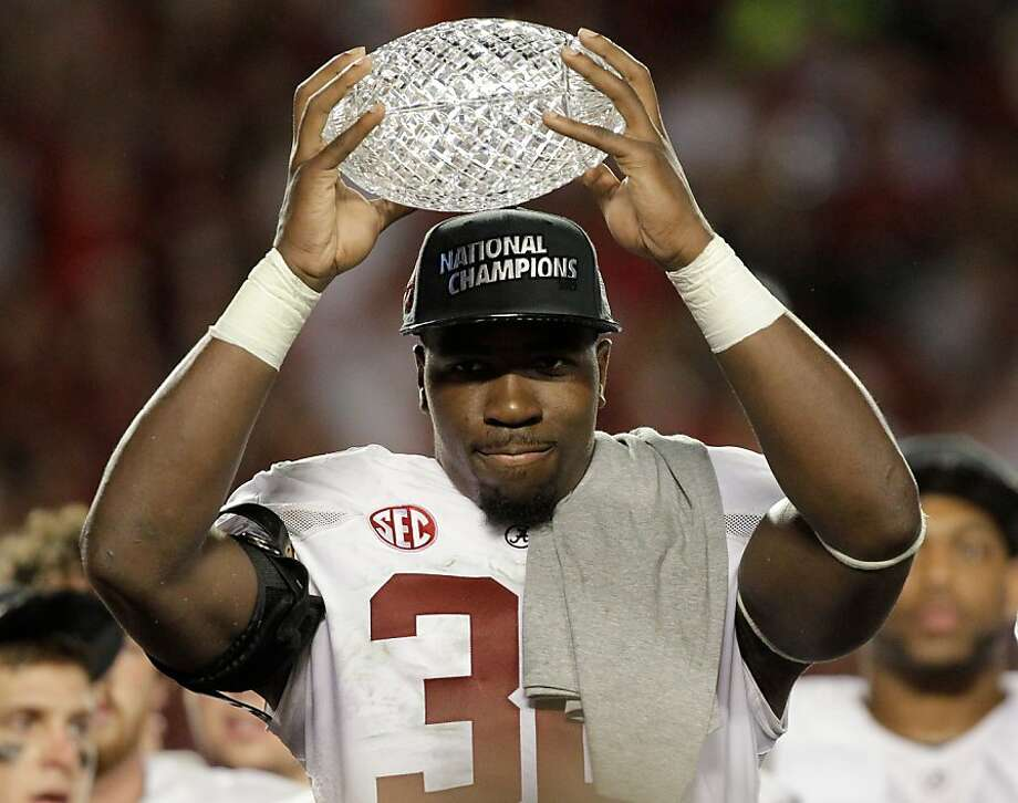 Alabama's C.J. Mosley holds up The Coaches' Trophy after the BCS National Championship college football game against Notre Dame Monday, Jan. 7, 2013, in Miami. Alabama won 42-14. (AP Photo/Chris O'Meara) Photo: Chris O'Meara, Associated Press